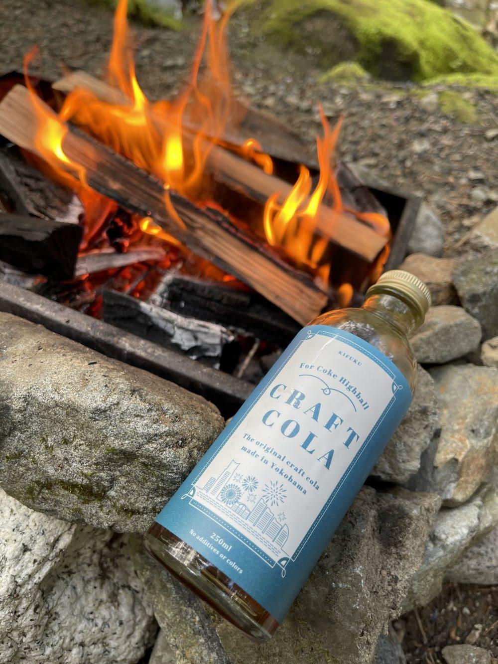 キャンプで焚火を囲みながらコークハイで乾杯